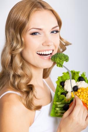 Portrait von glücklich lächelnden jungen schönen Frau mit gesunden vegetarischen Salat, über grauem Hintergrund Standard-Bild - 21460904