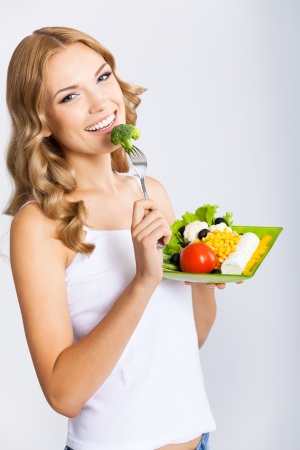 blondy: Portrait of happy smiling young beautiful woman with healthy vegetarian salad, over gray background Stock Photo