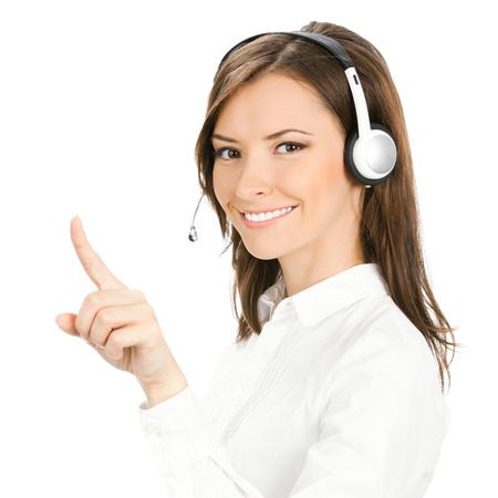 Retrato de feliz sonriente operador de tel?fono de atenci?n al cliente alegre en auriculares apuntando a algo, aislado sobre fondo blanco Foto de archivo