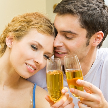 twenty two: Portrait of cheerful smiling couple with champagne, indoors Stock Photo