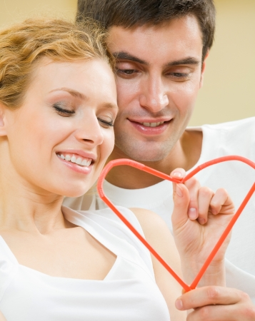 twenty two: Young amorous couple with heart symbol, made with cocktail tubules, indoor Stock Photo