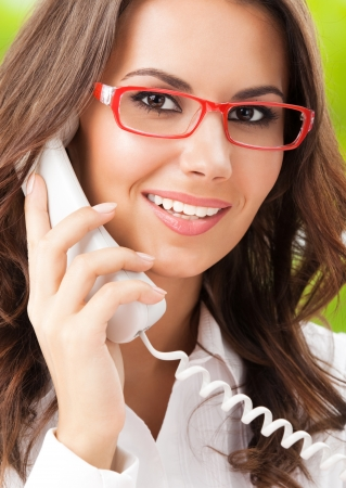 Portrait of happy smiling cheerful beautiful young business woman or support phone worker, at office Stock Photo - 21539379