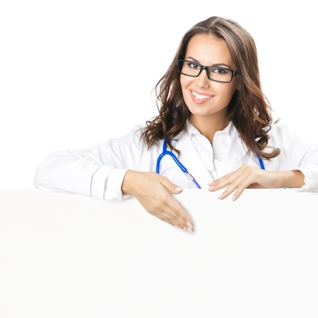 Portrait of happy smiling young female doctor showing blank signboard, isolated over white background photo