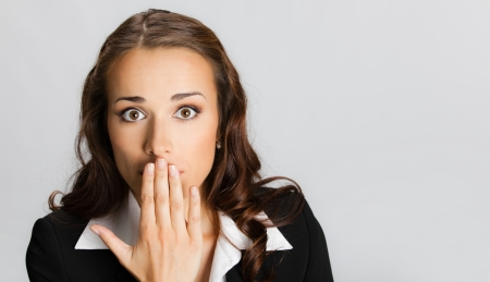 Portrait of surprised excited young business woman covering with hand her mouth, over gray background photo