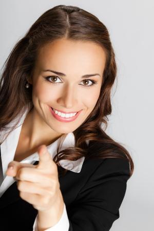 Portrait der jungen l?chelnden Gesch?ftsfrau zeigt mit dem Finger auf Betrachter, ?ber grauem Hintergrund Standard-Bild - 21694713