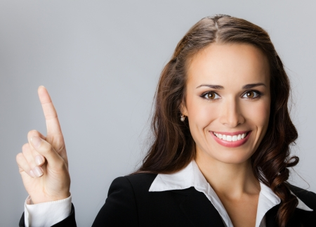 blank area: Happy smiling young business woman showing blank area for sign or copyspase, over grey background