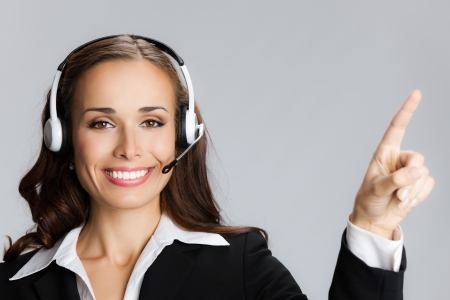 Portrait of happy smiling cheerful customer support phone operator in headset pointing at something, over grey background Stock Photo - 21694754