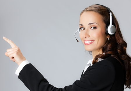 Portrait of happy smiling cheerful customer support phone operator in headset pointing at something, over gray background Stock Photo - 21694767