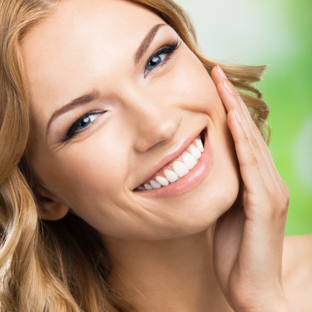 piel: Retrato de feliz sonriente mujer joven hermosa tocar la piel o la aplicaci?n de la crema, al aire libre