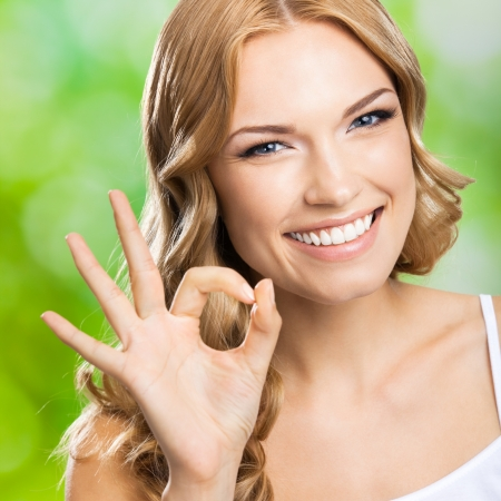 Portrait of beautiful young happy smiling blond woman with okay gesture, outdoors photo