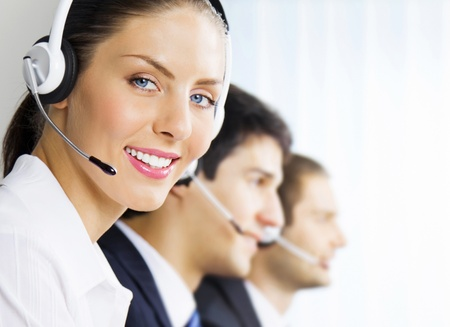 hotline: Three happy smiling young customer support phone operators at workplace Stock Photo
