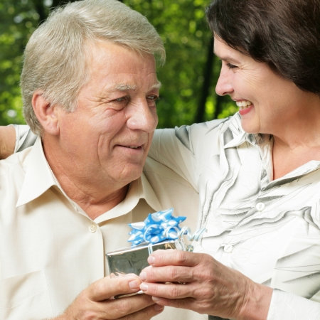 Mature happy smiling couple embracing in park with gift photo