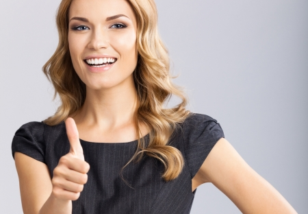 Happy smiling business woman with thumbs up gesture, on gray background photo