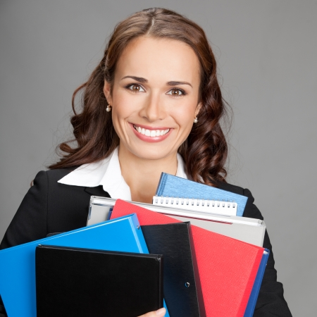 Portrait of happy smiling young busy business woman with folders, over gray background photo