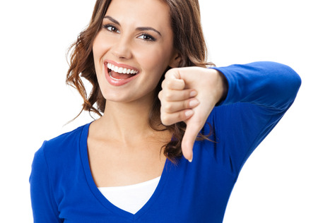 reject: Happy smiling beautiful young woman showing thumbs down gesture, isolated over white background