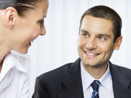 businessteam: Two smiling young businesspeople or businessman and client, working at office Stock Photo