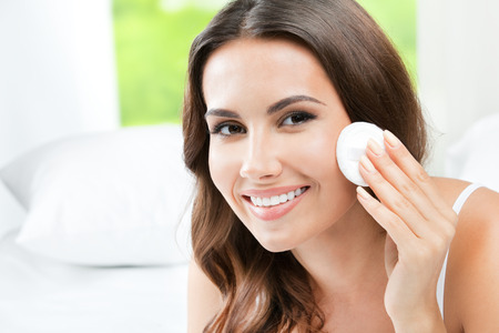 cotton pad: Portrait of happy smiling beautiful young woman cleaning skin by cotton pad Stock Photo