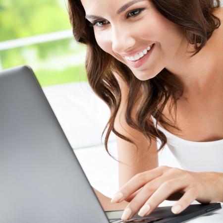Enthousiaste jeune femme utilisant un ordinateur portable Banque d'images