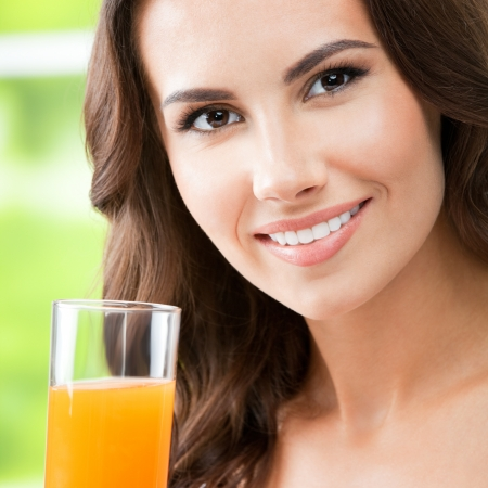 Portrait of happy smiling young beautiful woman drinking orange juice photo