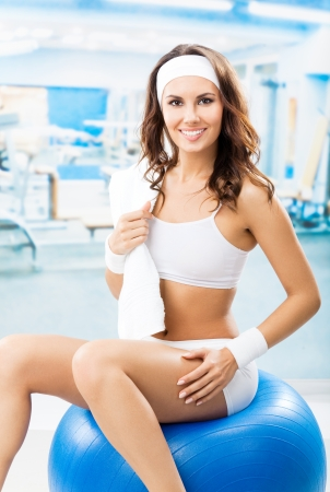Young cheerful smiling woman exercising with fitball at fitness club or gym photo
