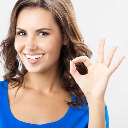 Portrait of young cheerful smiling woman showing okay gesture, over grey background photo
