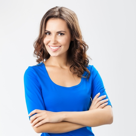 smiling woman: Portrait of young cheerful smiling woman, over grey background