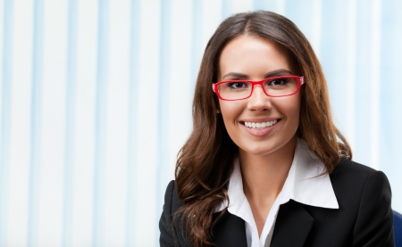 Portrait of happy smiling young cheerful business woman in glasses, at office photo
