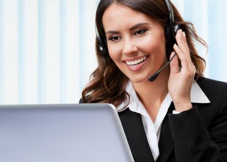 Portrait de sourire heureux jeune opérateur de support gai de téléphone dans le casque, travaillant avec un ordinateur portable, au bureau Banque d'images