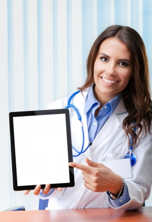 Portrait of happy smiling young female doctor showing blank tablet pc for copyspace, at office photo