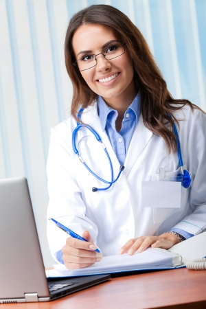 Portrait of cheerful female doctor working with laptop at office photo