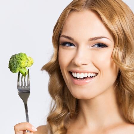 brocoli: Retrato de la sonrisa feliz de la mujer hermosa joven que come el brócoli, sobre fondo gris