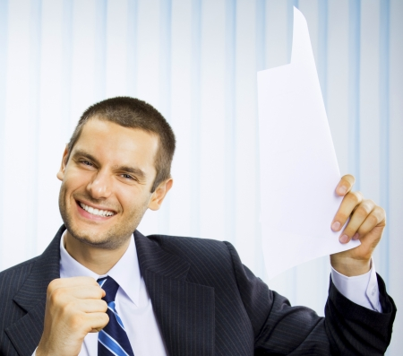 Happy successful gesturing businessman with document at office photo