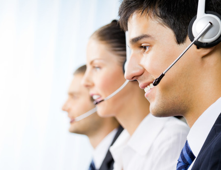 call center: Three happy customer support phone operators at office Stock Photo