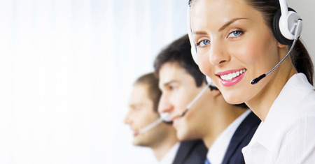 Three happy smiling young customer support phone operators at workplace, with copyspace Stock Photo