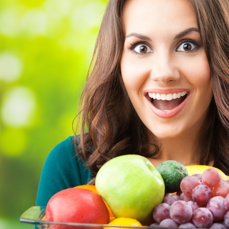 Young happy smiling woman with plate of fruits, outdoors Imagens
