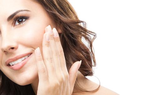 白い背景の上の肖像画の幸せな笑顔の美しい若い女性の肌に触れるか、クリームを適用する分離