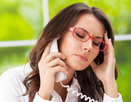 distraught: Thinking, tired or ill with headache business woman with phone at office