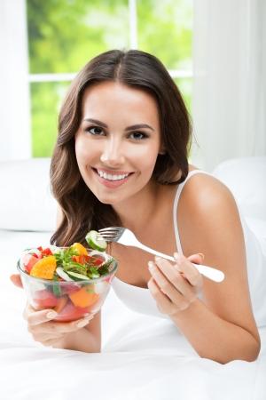 Portrait de jeune femme souriante heureuse avec salade de légumes végétarien, à l'intérieur