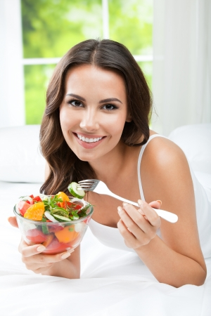 diets: Portrait of happy smiling young woman with vegetarian vegetable salad, indoors Stock Photo