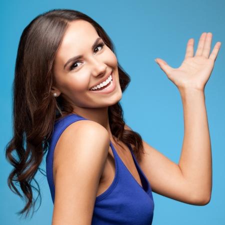 Portrait der freundlichen Geste lächelnden jungen Frau, über blauem Hintergrund Standard-Bild - 24369732