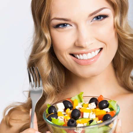 Portrait of happy smiling young beautiful woman with healthy vegetarian salad, over gray background photo