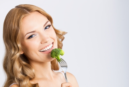 Portrait of happy smiling young beautiful woman eating broccoli, over gray background photo