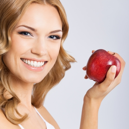 Portrait of happy smiling young beautiful woman with red apple, over gray background photo