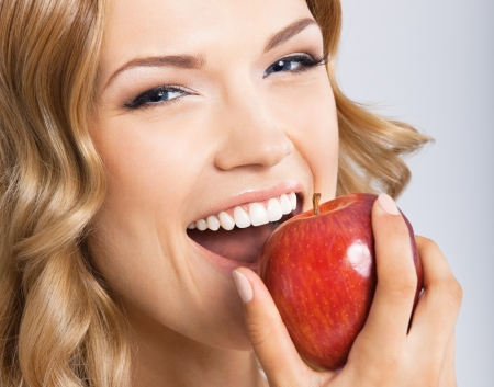 Portrait of happy smiling young beautiful woman eating red apple, over gray background photo