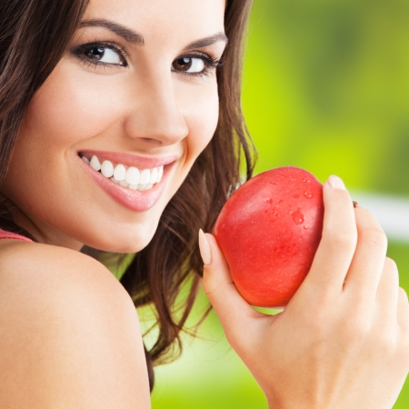 Portrait of young woman with red apple, outdoors photo