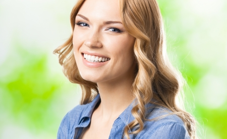 Portrait of beautiful young happy smiling blond woman with long hair photo