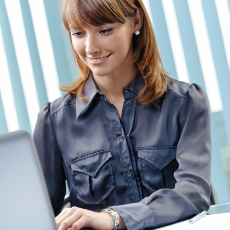 Portrait of happy young business woman working with laptop at office photo