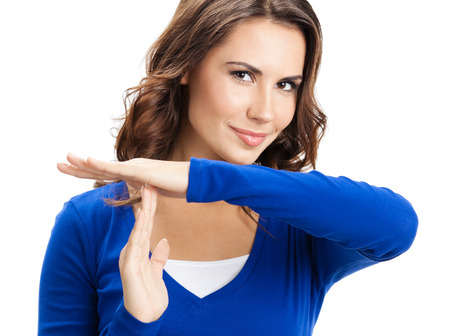 Happy smiling beautiful young woman showing time out gesture, isolated over white background photo