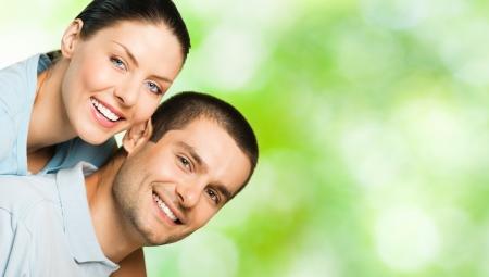 part of me: Young feliz sonrisa atractiva pareja, al aire libre. Para proporcionar la máxima calidad, he hecho esta imagen, por la combinación de tres fotos. Puede utilizar la parte izquierda para lema, texto grande o banner.  Foto de archivo
