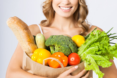 healthy girls: Portrait of happy smiling young beautiful woman holding grocery shopping bag with healthy vegetarian raw food, over gray wall  Stock Photo